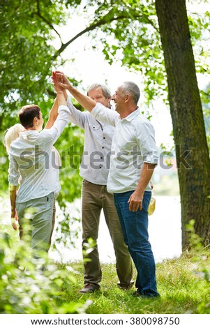 Team group in nature giving high five in summer - stock photo