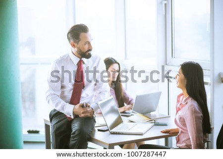 Team lead sitting on table next to manager. Office concept.