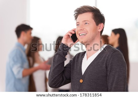 Team leader on the phone. Handsome young man talking on the mobile phone and smiling while group of people communicating on background - stock photo