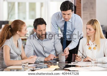 Team leader pointing charts and graphs on digital tablet. Businesspeople working as a team in the office. Businesspeople working together and discussing about new ideas for marketing. - stock photo