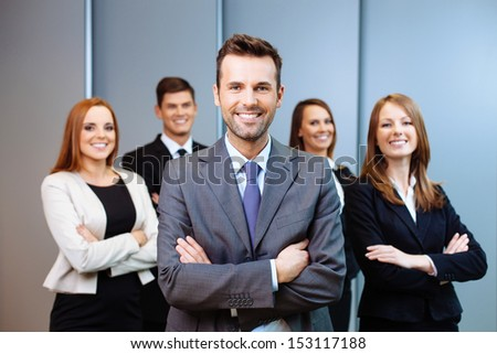 Team leader stands with coworkers in background