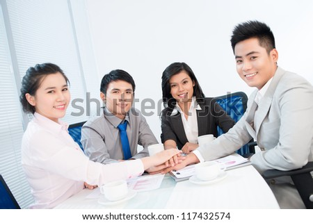 Team members supporting each other to achieve better business results - stock photo