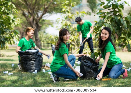 Team of activists collecting litter in the park - stock photo