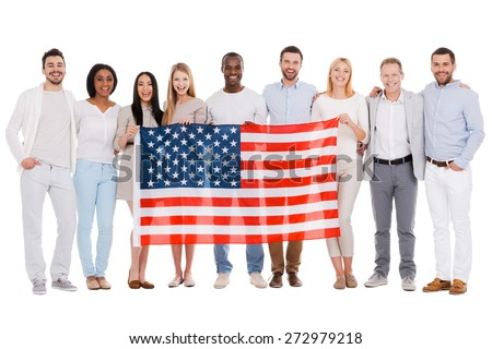 Team of America. Full length of happy diverse group of people bonding to each other and holding flag of America while standing against white background together - stock photo