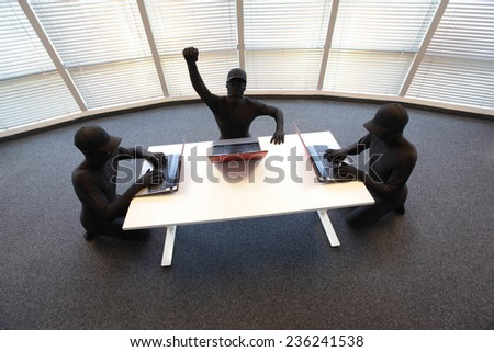 team of anonymous hackers in black costumes working with computers in office - stock photo