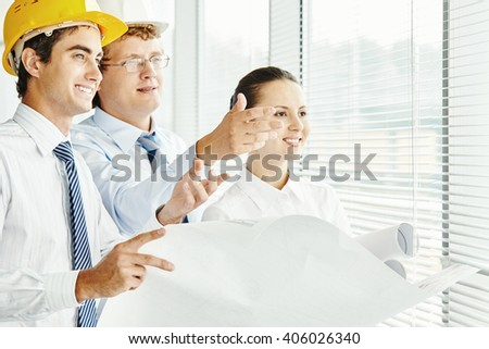 Team of architects discussing a new housing project - stock photo
