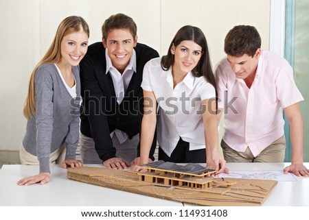 Team of architects standing around 3D building model in their office - stock photo
