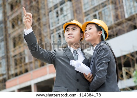 Team of architects wearing hardhats studying the exterior of the building - stock photo