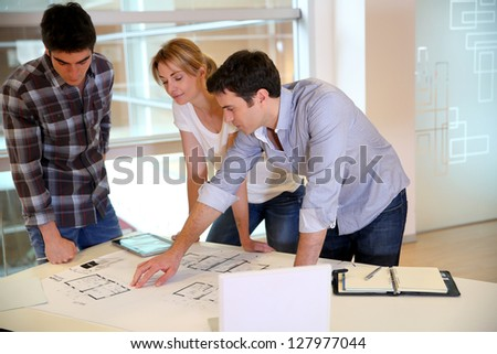 Team of architects working on construction plans - stock photo