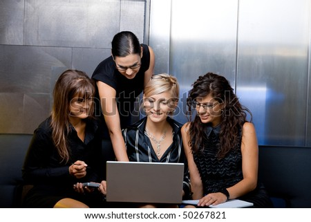 Team of attractive businesswoman having a meeting sitting on couch, using laptop computer, smiling. - stock photo