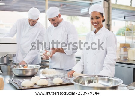 Team of bakers working at counter in the kitchen of the bakery - stock photo