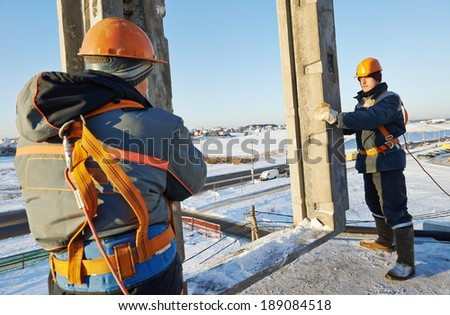 Team of builder worker in safety protective equipment at winter construction site - stock photo