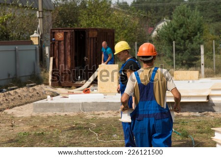 Team of builders or workmen on site at a new build house construction installing the insulated wooden wall panels - stock photo