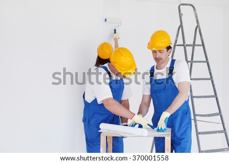 Team of builders with construction plan indoors