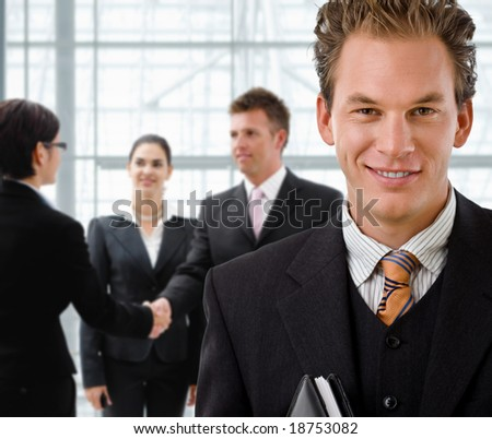 Team of business people, businessman in front, handsake in background. - stock photo