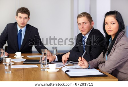 Team of 3 business people during meeting, sitting at big conference table - stock photo