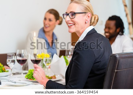Team of business people eating in restaurant, food and wine on the table - stock photo