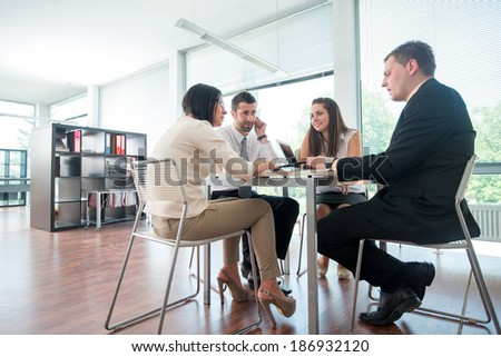 Team of business people sitting around table in office