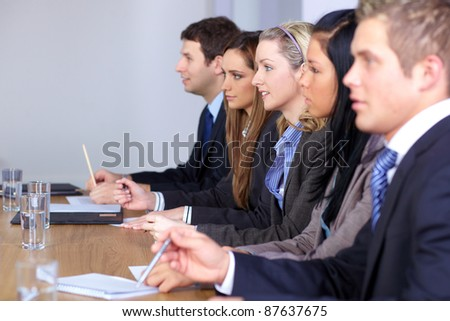 Team of 5 business people sitting at conference table, focus on blonde female - stock photo
