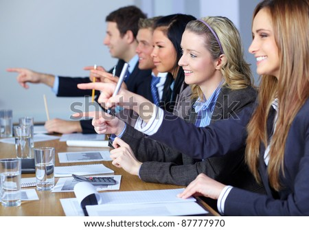 Team of 5 business people sitting at conference table point forward with their fingers,