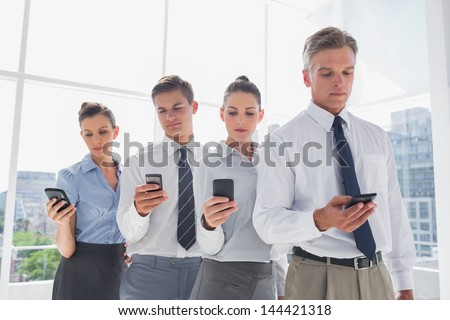Team of business people standing together in line with their mobile in a modern office - stock photo