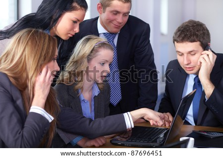 Team of 5 business people working on laptop, one male and one female talks over mobile phones - stock photo