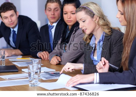 Team of 5 business people working on some calculations, calculator and come documents on conference table, focus on blonde female - stock photo