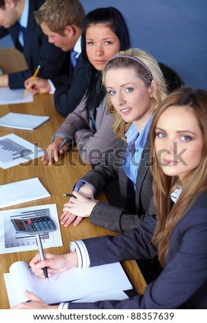 Team of 5 business people working on some calculations, focus on blonde female looking up to camera - stock photo