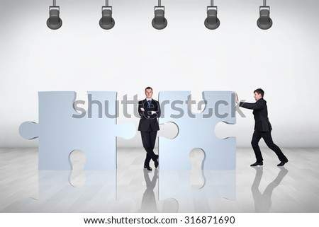 Team of business people working together and try to join puzzle in the grey room. - stock photo