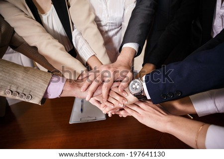 Team of  businessmen with folded hands, a symbol of teamwork