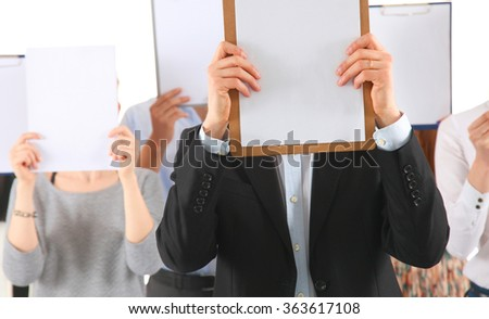 Team of businesspeople holding a folders near face isolated on white background