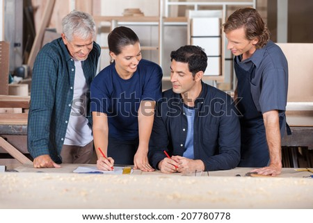 Team of carpenters working together on blueprint at table in workshop - stock photo