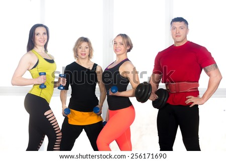Team of cheerful sporty people, friends, instructors in fitness club lifting dumbbells. Well-built powerlifter and three female athletes doing weight training in gym - stock photo