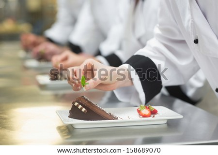 Team of chefs in a row garnishing dessert plates in a busy kitchen - stock photo