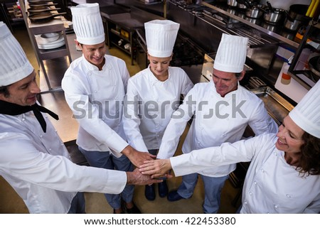 Team of chefs putting hands together and smiling in a commercial kitchen - stock photo