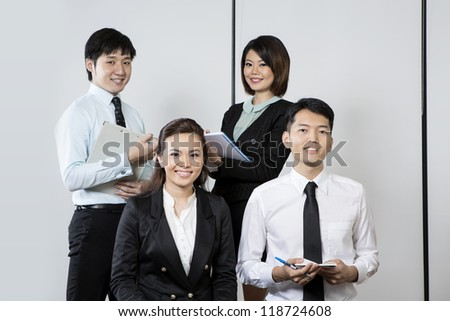 Team of Chinese Business people in there office. - stock photo