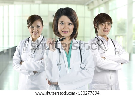 Team of Chinese doctor's wearing a white coat and stethoscope. Three Asian doctors wearing lab white coats standing in a hospital. - stock photo