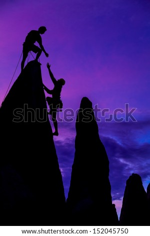Team of climbers conquer the summit of a challenging rock spire. - stock photo