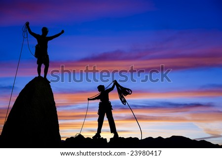 Team of climbers silhouetted as they coil ropes after reaching the summit of a rock pinnacle in The Sierra Nevada Mountains, California. - stock photo