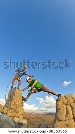 Team of climbers struggle to the summit of a rock pinnacle after a challenging ascent.