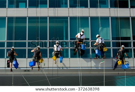 Team Of Climbing Workers Cleaning an Office Building - stock photo