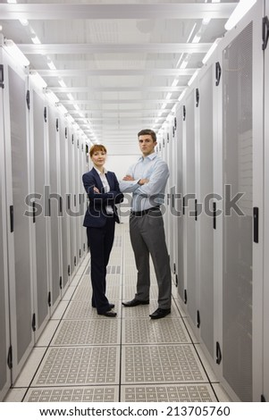 Team of computer technicians smiling at camera in large data center - stock photo