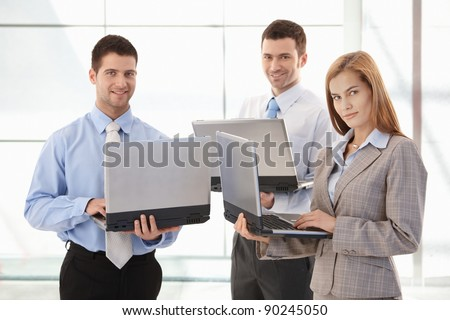 Team of confident businesspeople working on laptop in office lobby, smiling.?