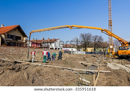 Team of construction workers are preparing site for concreting. Construction workers are adjusting scaffolding made of planks for casting concrete. - stock photo