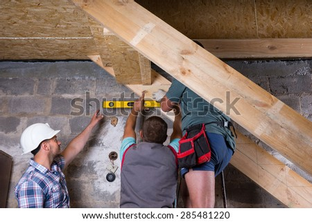 Team of Construction Workers Building Wooden Staircase Frame in Unfinished Basement of New Home, Checking Levels for Accuracy and Quality Control - stock photo