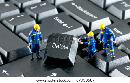 Team of construction workers working with DELETE button on a computer keyboard - stock photo