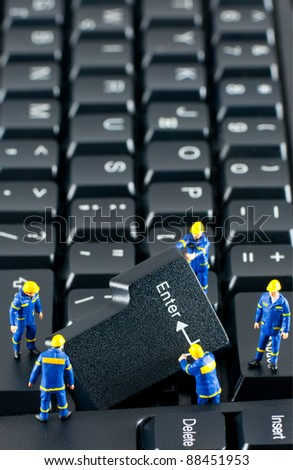 Team of construction workers working with ENTER button on a computer keyboard