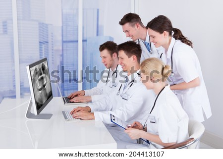 Team of dentists examining jaw Xray on computer in hospital