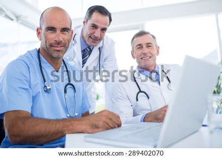 Team of doctor looking at camera in medical office - stock photo