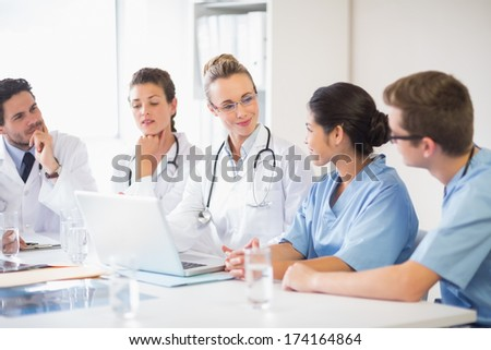 Team of doctors and nurses discussing in hospital - stock photo